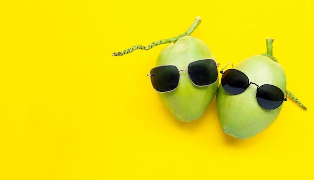 Два молодых oconut с очками на желтом фоне. наслаждайтесь концепцией летнего отдыха.