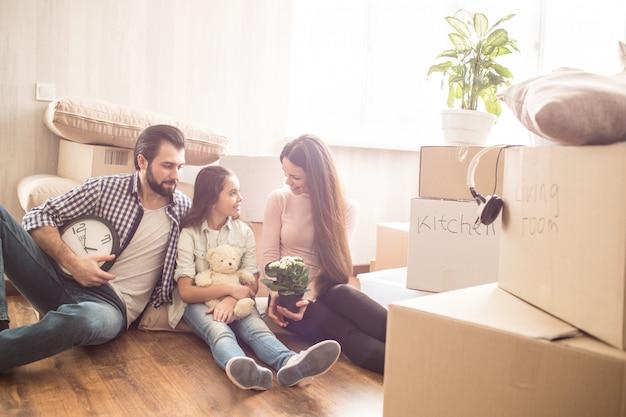 Двое молодых родителей сидят на полу и смотрят на своего ребенка. они окружены волами, полными вещей для кухни и гостиной. они проводят время друг с другом и разговаривают.
