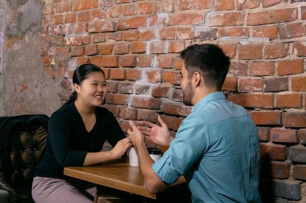 荒いレンガの壁を背景にカフェのテーブルに座って何か楽しいことを話している2人の若者男と女