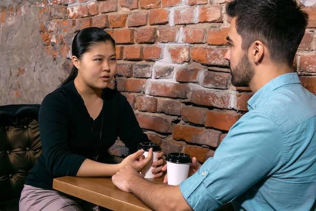 荒いレンガの壁の背景にあるカフェのテーブルに座って、深刻なことについて話している男と女の2人の若者