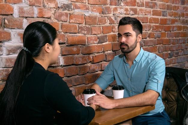 荒いレンガの壁の背景にある喫茶店で手をつないで話している2人の若者男と女