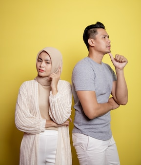 2人の若者、女性のヒジャーブと黄色の壁に隔離された表現を考えている男性