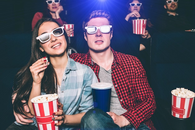 Two young people are sitting close to each other. they have special glasses on their faces to watch movie. girl is holding basket with popcorn and one piece of it in her hands. man has a cup of coke