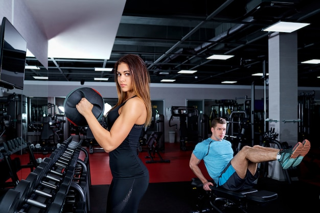 Two young people doing exercises in the gym.