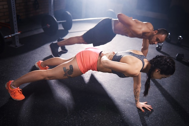 Two young people doing push ups together