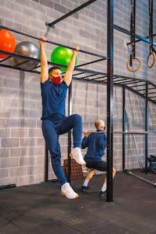 새로운 정상인 코로나 바이러스 전염병으로 체육관에서 운동하는 두 젊은이.