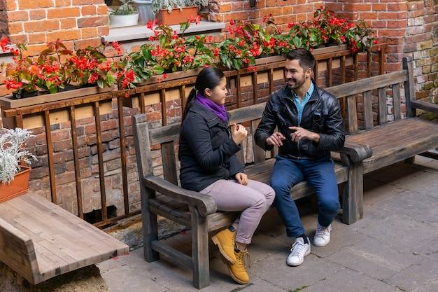 Two young people a guy and a girl are having fun discussing something, sitting on a bench outdoors