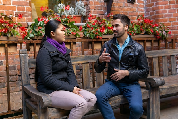 Two young people a guy and a girl talking gesturing sitting on a bench outdoors