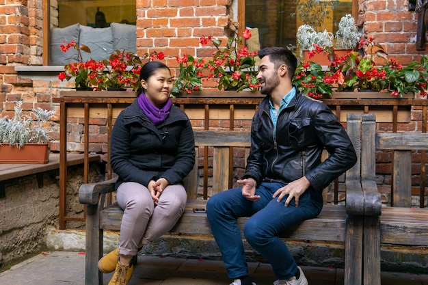 Two young people a guy and a girl talking sitting on a bench outdoors