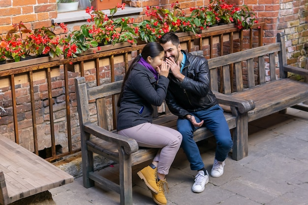 Two young people a guy and a girl whisper about something and laugh sitting on a bench outdoors