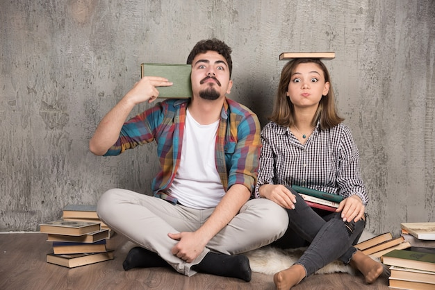 Due giovani in posa carino con un mucchio di libri