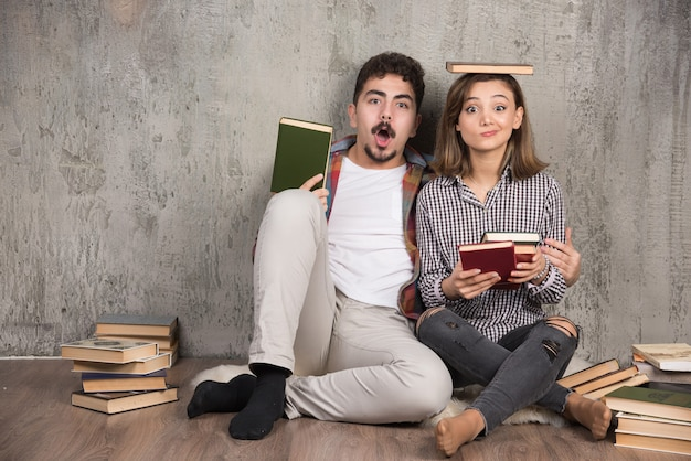 Due giovani in posa con un mucchio di libri