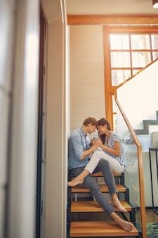 서로의 손을 잡고있는 동안 두 젊은 사람들이 럭셔리 현대 집에서 함께 휴식
