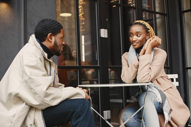 外に座っている2人の若者。お互いに過ごす時間を楽しんでいるアフリカのカップル。