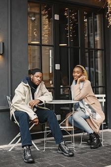Due giovani seduti fuori. coppie africane che si godono il tempo trascorso insieme.