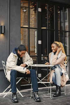 Two young people sitting outside. african couple enjoying the time spending with each other.