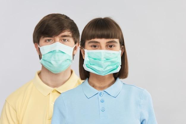 회색 벽에 보호 호흡 마스크를 착용하는 두 젊은 사람