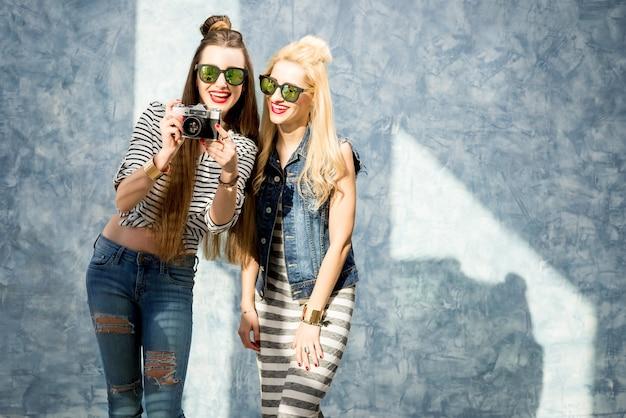 青い壁の背景にレトロな写真カメラを持つ2人の若い写真家