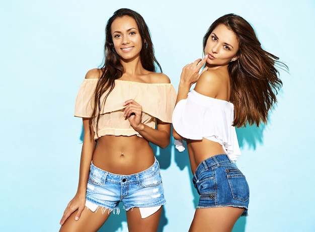 Two young playful hipster women in trendy summer jeans shorts clothes. sexy carefree brunette women models posing near blue wall