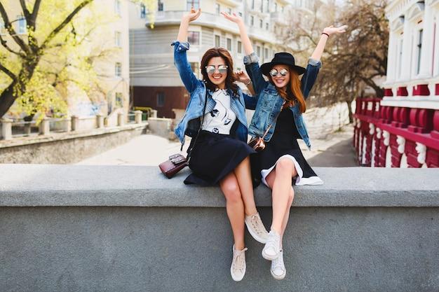 Две молодые красивые подруги женщины веселятся на улице на улице