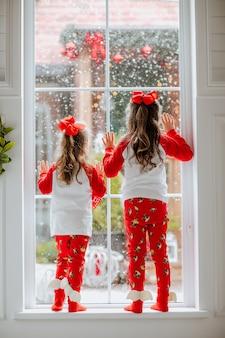 Две молодые красивые девушки в красно-белых рождественских пижамах и бантах позируют на большом окне