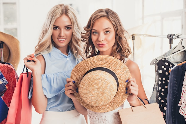 Two young pretty girls looking at dresses and try on it while choosing at shop