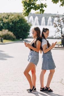 Две молодые красивые девушки на прогулке в парке с телефонами