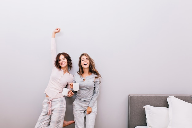 Two young pretty girls in pajamas with cups in sleeping room on grey wall . they having fun and smiling .