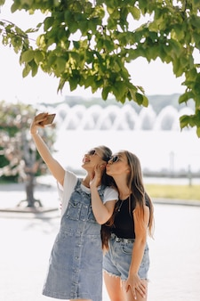 Two young pretty girls on a walk in the park taking pictures of themselves on the phone