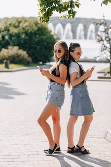 Two young pretty girls on a walk in the park with phones. sunny summer day, joy and friendships.