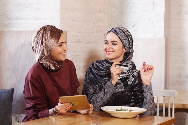 Two young pretty muslim women talk and shop online using an electronic tablet