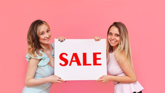 Две молодые симпатичные улыбающиеся женщины держат белый плакат со словом распродажа на розовом фоне