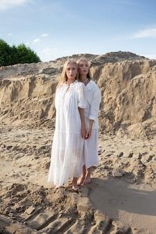 우아한 흰색 드레스에 모래 채석장에서 포즈를 취하는 긴 금발 머리를 가진 두 젊은 예쁜 쌍둥이