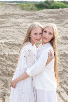 Две молодые симпатичные близнецы с длинными светлыми волосами позируют на песчаном карьере в элегантных белых платьях