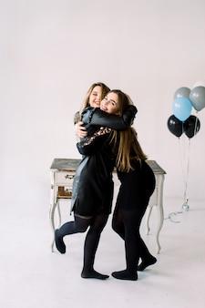 空気バルーンを一緒に保持している黒のドレスの2人の若いきれいな女性、白で隔離されるクローゼットとビンテージの白いテーブルの近くの鶏や誕生日のパーティースタンディングを祝う