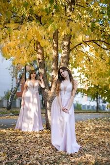 가 공원에서 좋은 베이지색 드레스를 입고 두 젊은 공주. 패션 사진입니다.