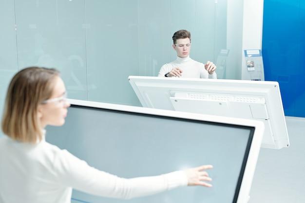 Два молодых прогрессивных разработчика программного обеспечения просматривают базу данных на больших интерактивных дисплеях, работая индивидуально в офисе
