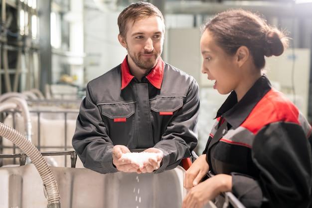 Два молодых менеджера по контролю качества обсуждают характеристики белых пластиковых гранул, в то время как один из них держит стопку над большим контейнером