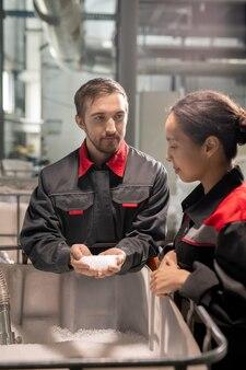 Два молодых менеджера по контролю качества в спецодежде обсуждают характеристики белых пластиковых гранул, в то время как один из них держит стопку над контейнером