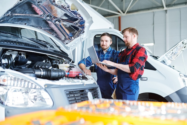 Two young repairmen in workwear standing by car engine and consulting websites for maintenance information
