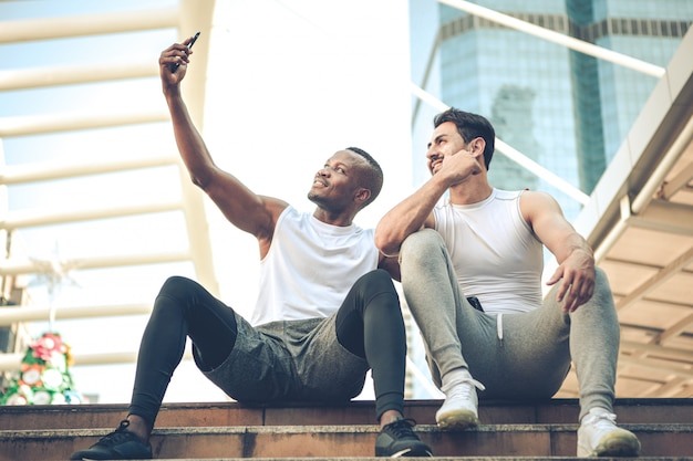 Two young runners sat to rest and took a selfie with a smile on the stairs.