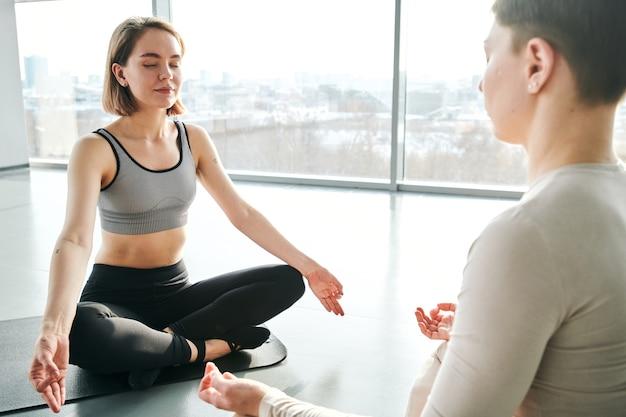 로터스의 포즈에 매트에 앉아서 연습하는 activewear 두 젊은 고요한 여성은 체육관에서 요가 운동을 이완