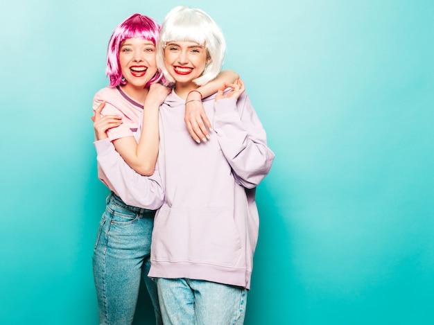 Две молодые сексуальные хипстерские девушки в париках и красных губах. красивые модные женщины в летней одежде. беззаботные модели, позирующие у синей стены в студии