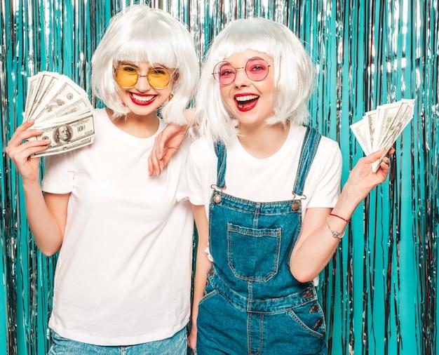 Due giovani ragazze sexy dei pantaloni a vita bassa in parrucche bianche e labbra rosse belle donne che tengono i dollari nelle mani di estate che spendono soldi