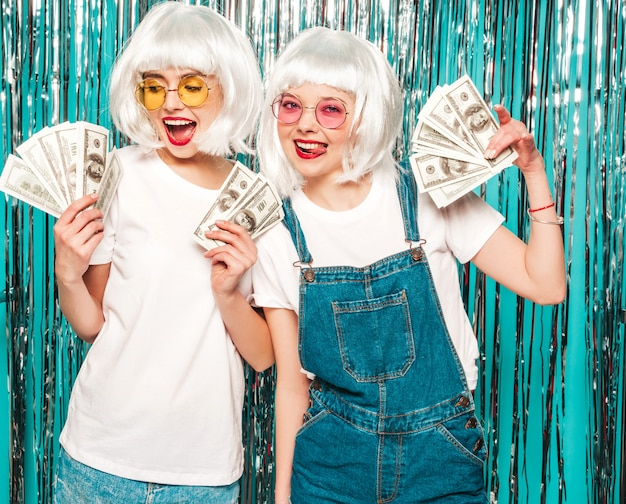 Two young sexy hipster girls in white wigs and red lips.beautiful women holding dollars in hands summer  spending money