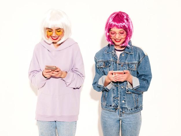 Due giovani ragazze sexy hipster in parrucche e labbra rosse. belle donne alla moda in abiti. si digitano sms a vicenda. utilizzando smartphone
