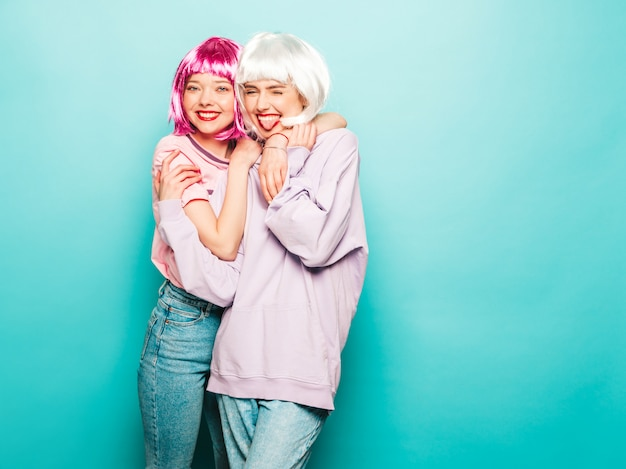 Due giovani ragazze sexy hipster in parrucche e labbra rosse. belle donne alla moda in abiti estivi. modelle vivaci in posa vicino alla parete blu in studio impazzendo. mostra la lingua