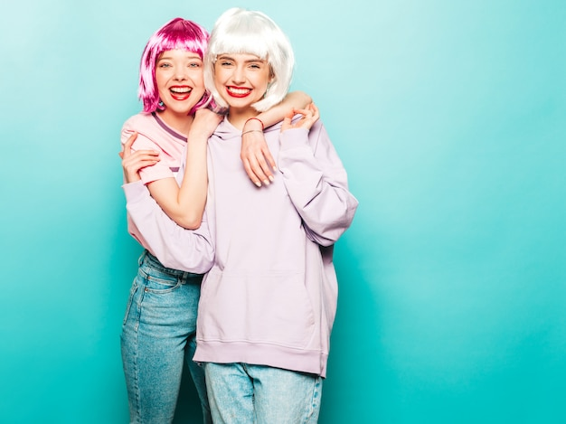 Two young sexy hipster girls in  wigs and red lips.beautiful trendy women in summer clothes.carefree models posing near blue wall in studio going crazy