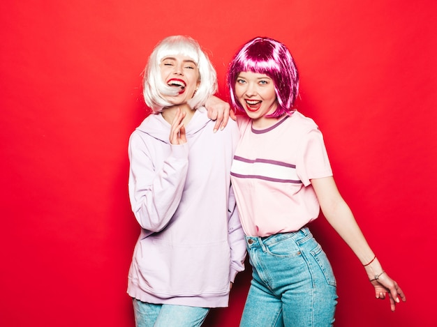 Two young sexy smiling hipster girls in white wigs and red lips.beautiful trendy women in summer clothes.carefree models posing near red wall in studio going crazy