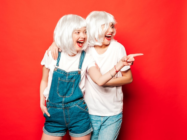 Two young sexy smiling hipster girls in white wigs and red lips.beautiful trendy women in summer clothes.carefree models posing near red wall in studio summer  pointing on shop sales